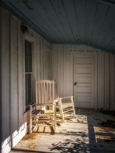 Abandoned rocking chairs on screened porch of proprietors residence